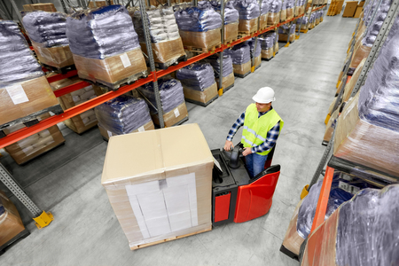 logistic business, shipment and people concept - loader operating forklift and loading boxes at warehouse