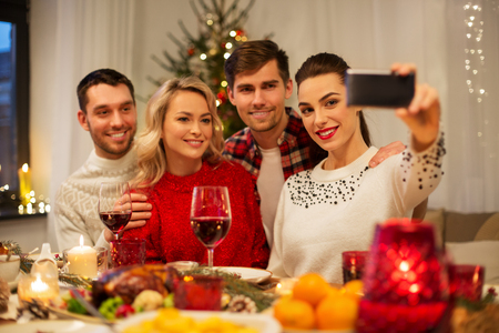 holidays and celebration concept - happy friends taking selfie by smartphone at home christmas dinner Stock Photo