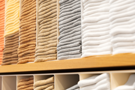 close up of shelves with clothes at clothing store Stock Photo