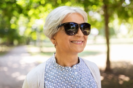 old age, eyewear and people concept - portrait of happy senior woman in sunglasses at summer park Banco de Imagens