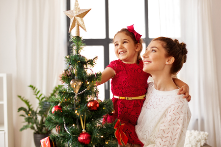 mother and daughter decorating christmas tree 스톡 콘텐츠
