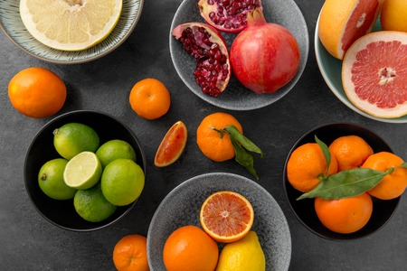 close up of citrus in bowls fruits on stone table 免版税图像