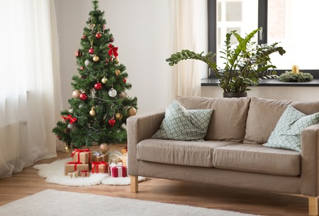 christmas tree, gifts and sofa at cozy home