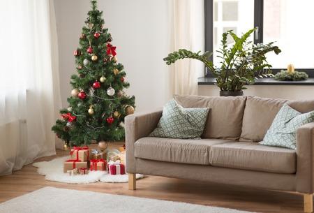 kerstboom, cadeaus en bank bij gezellig thuis Stockfoto