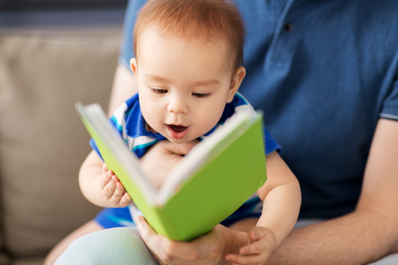 close up of baby boy and father with book at home Фото со стока