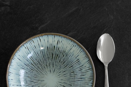 close up of ceramic plate and spoon on table