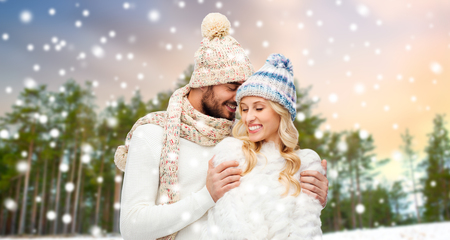 winter, christmas and people concept - happy couple in hats and scarf hugging over forest background