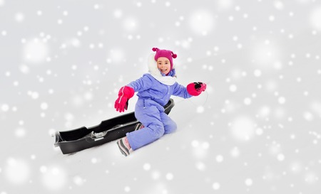 little girl with sled on snow hill in winter Stock Photo