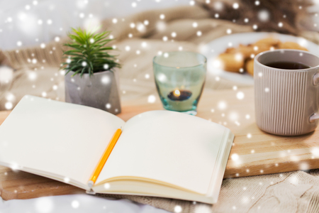 diary, tea and candle in holder at home over snow