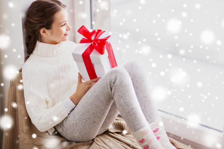 girl with christmas gift sitting on sill at window