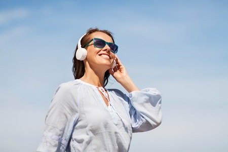 woman with headphones over blue sky