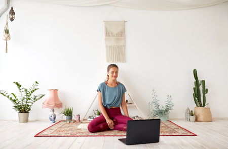 woman with laptop computer at yoga studio