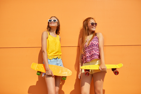 teenage girls with short skateboards in city