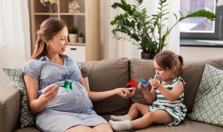 madre incinta e figlia con origami di gru