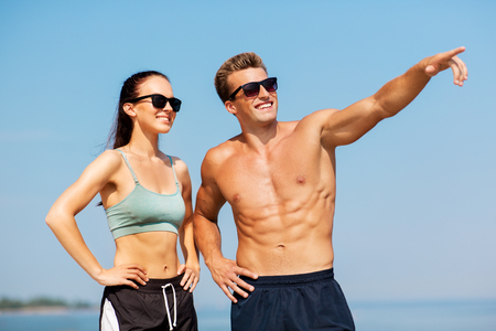 happy couple in sports clothes and shades on beach 免版税图像 - 110753151