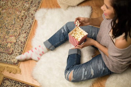 happy woman eating popcorn at home