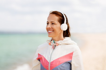 smiling woman with headphones on beach 写真素材
