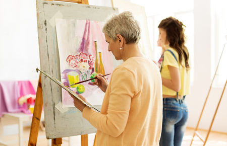 senior woman painting at art school studio
