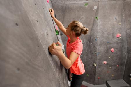 young woman exercising at indoor climbing gym wall