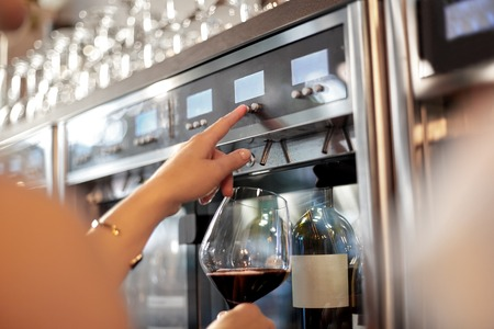 close up of woman with glass at wine dispenser Zdjęcie Seryjne