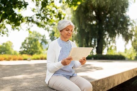 senior woman reading newspaper at summer park