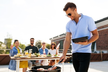 man cooking meat on bbq at rooftop party Stock Photo