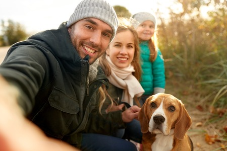 happy family with dog taking selfie in autumn