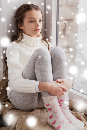 sad girl sitting on sill at home in winter