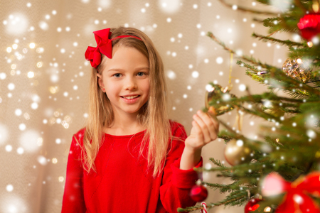happy girl in red decorating christmas tree