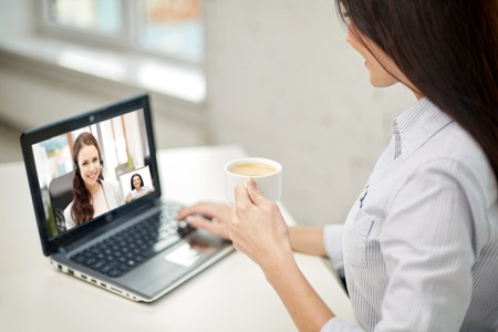 woman drinking coffee having video call on laptop