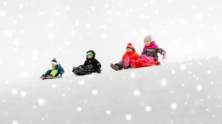 kids sliding on sleds down snow hill in winter Stockfoto