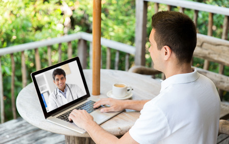 man having video chat with doctor on laptop Stock Photo