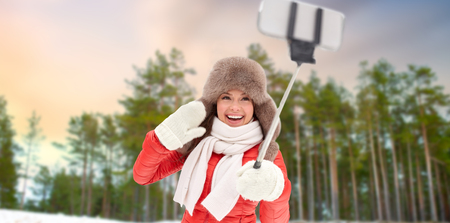 happy woman taking selfie over winter forest