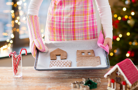 woman with gingerbread house parts on oven tray
