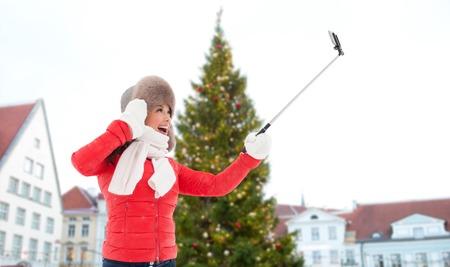 woman taking selfie over christmas tree Stock Photo