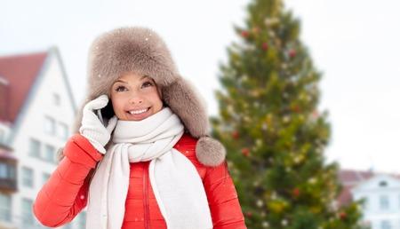 woman calling on smartphone over christmas tree