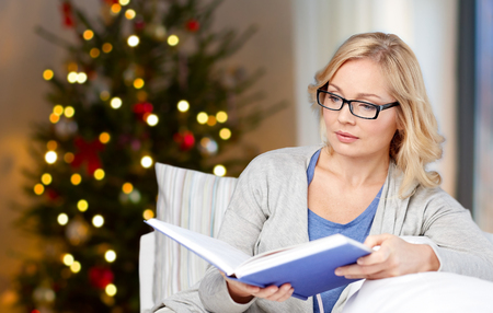 woman in glasses reading book on christmas
