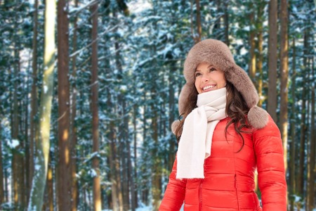 happy woman in fur hat over winter forest Stock Photo
