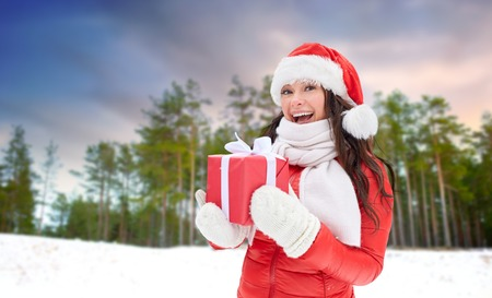 happy woman in santa hat with chrismas gift