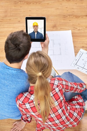 repair, building and technology concept - close up of couple with blueprints having video call with builder or foreman on tablet pc computer at home