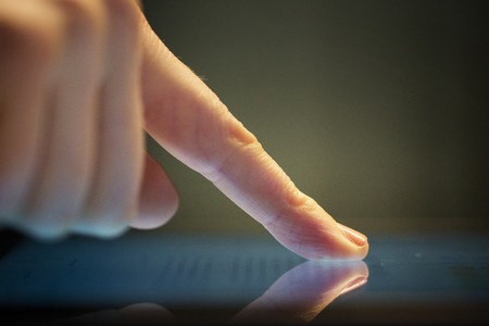 close up of hand using computer touch screen