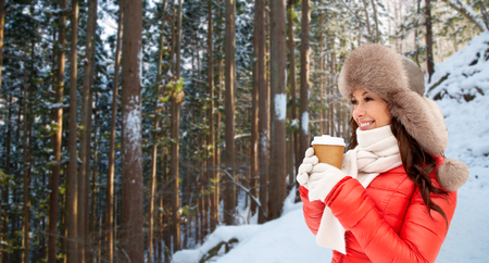 woman in fur hat with coffee over winter forest Stock Photo
