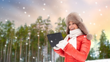 woman in fur hat with tablet pc over winter forest Stock Photo