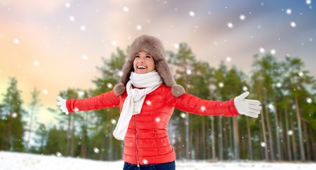 happy woman in fur hat over winter forest and snow