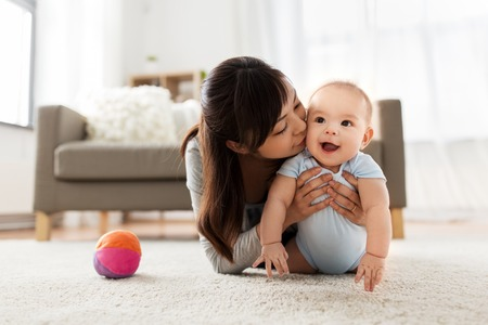 happy young mother kissing little baby at home Stock Photo