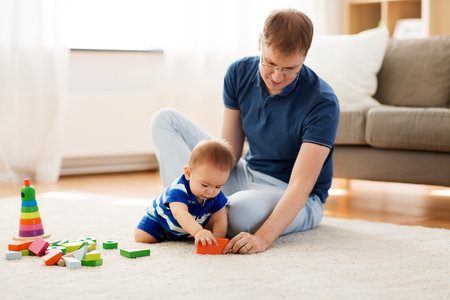 happy father with baby son playing toys at home Stock Photo