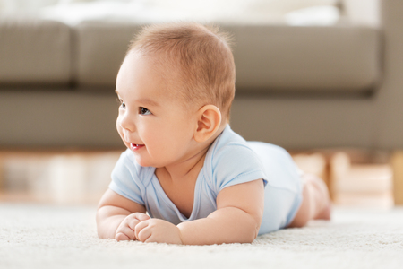 sweet little asian baby boy lying on floor at home
