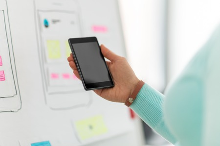 ui designer or developer hand holding smartphone