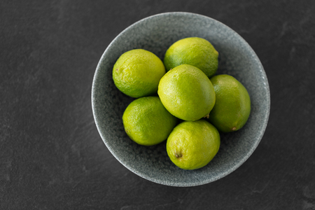 close up of whole limes in bowl on slate table top Stock Photo