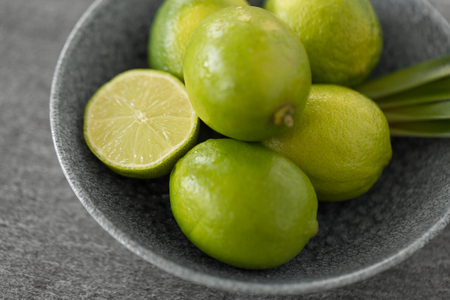 close up of limes in bowl on slate table top